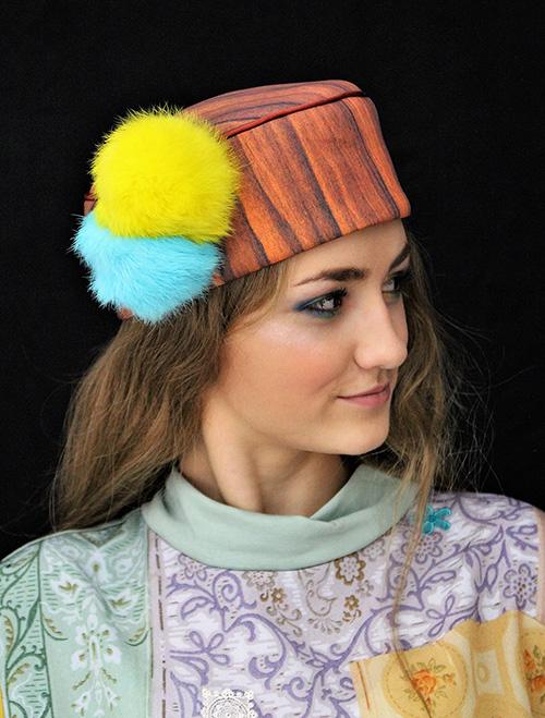 Holzkappe mit Bommeln in gelb und türkis mit Modell
